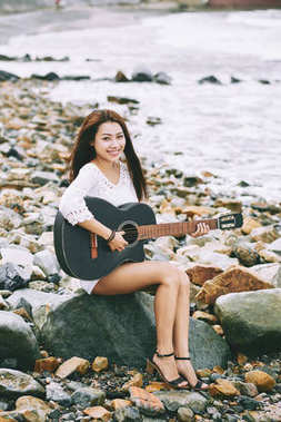 Beautiful Vietnamese girl sitting on rocks by the sea and playing guitar