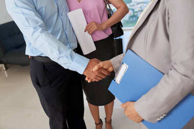 Close-up image of broker and couple shaking hands after meeting