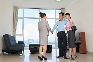 Woman showing apartment for rent to cheerful couple