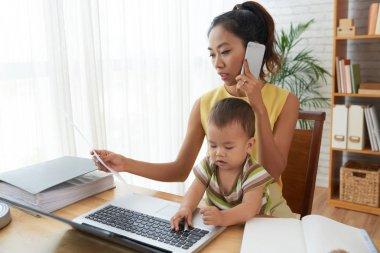 Çalışma from Home, Vietnamca genç kadın bebek dizüstü bilgisayarda oynuyor