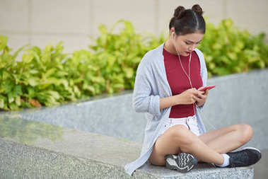 Young Asian woman sitting outdoors and using music application in her smartphone