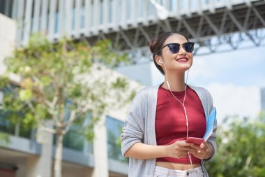 Young smiling woman in sunglasses enjoying sunny day in the city