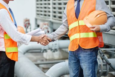 Cropped image of plant engineers in orange vests shaking hands