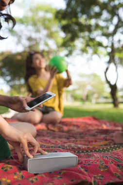 Close-up image of girl using smartphone and portable speaker at picnic