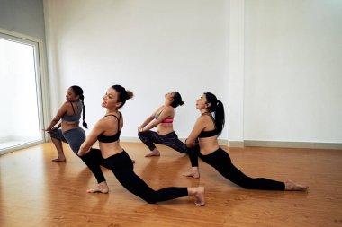 sportive women in sportswear practicing performance in dancing studio