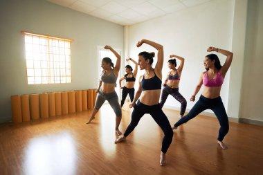 sportive women in sportswear practicing choreography in dancing studio
