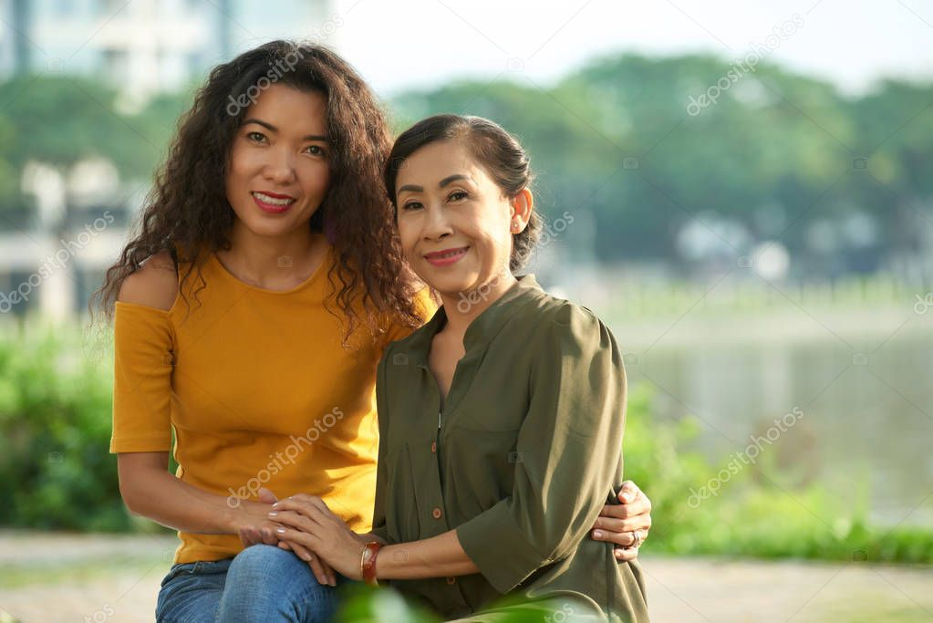 Portrait shot of attractive middle-aged woman and her mature Asian mother at public park