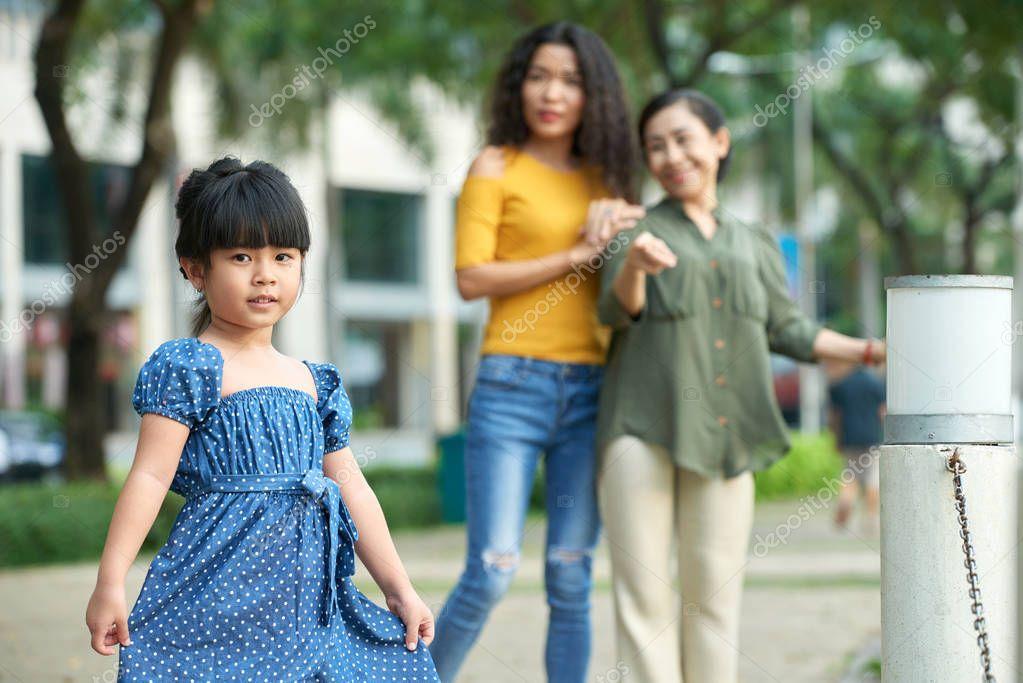 Adorable little girl wearing polka dot dress, mother and senior grandmother standing behind