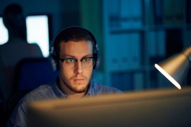 Software developer listening to music and working on computer late at night