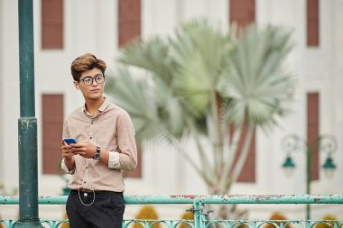 Attractive Vietnamese young man with smartphone standing in the street and listening to music