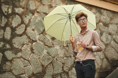Young Asian man walking with yellow umbrella and listening to music
