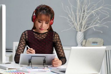 Asian graphic designer sitting at office desk and listening to music in headphones