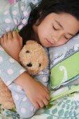 Fotografie Malá holčička objímání její Medvídek, když spí