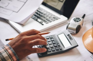 Hands of engineer calculating budget estimate for project