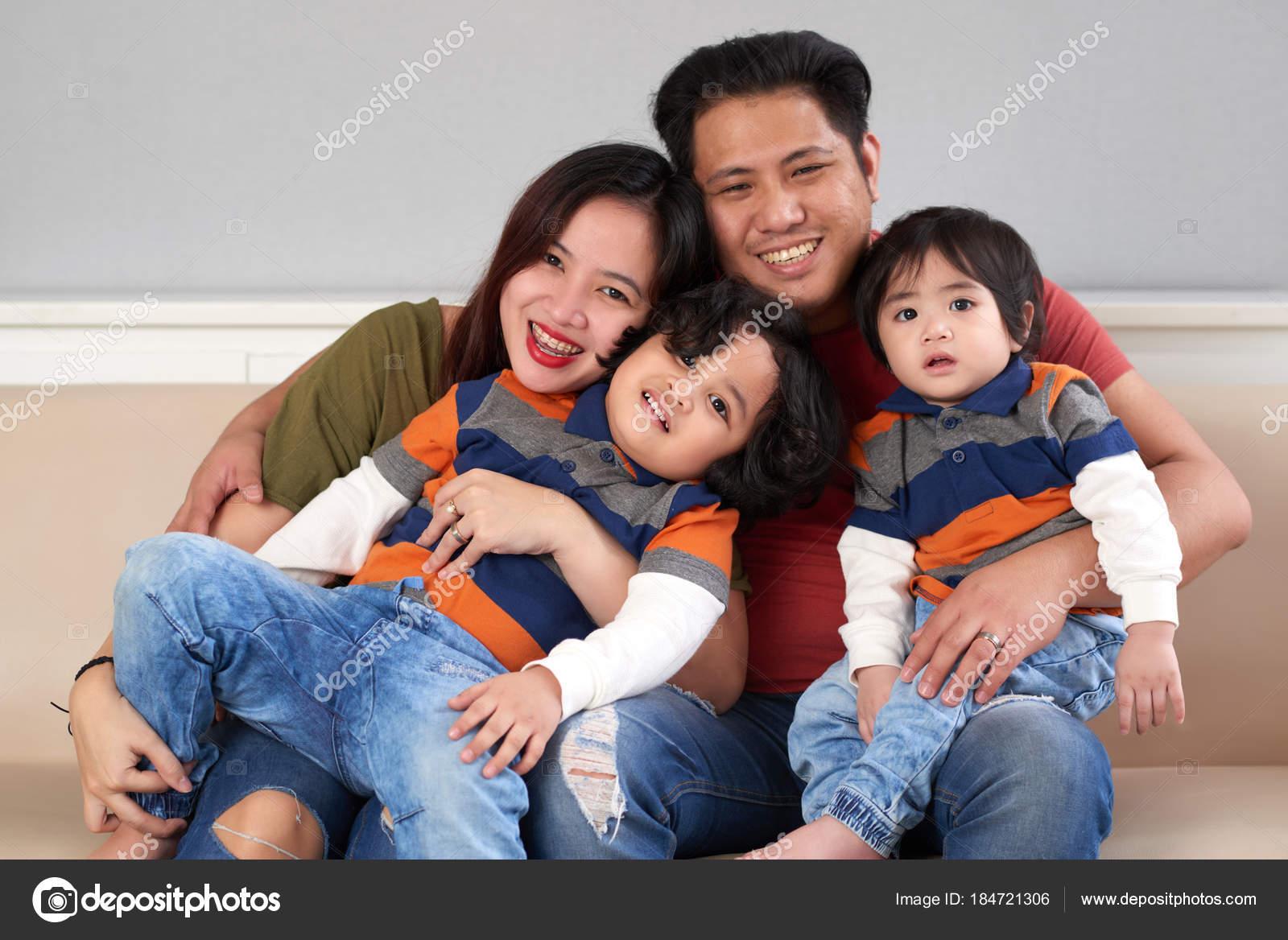 happy filipino man hugging his wife two children stock photo