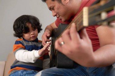 Asian man teaching his son how to play guitar