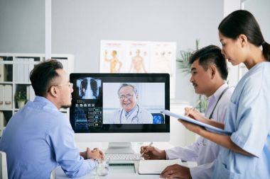 Asian medical interns consulting with doctor online