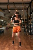 Female Muay Thai fighter having training in gym