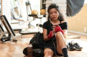 Photo Female listening to music on her smartphone after training in gym