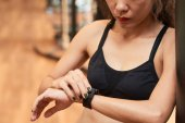 fit woman setting her smart watch before training