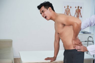 Young man suffering form severe pain in his low back