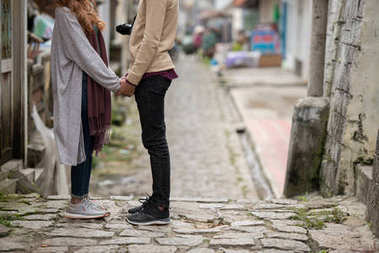 Cropped image of couple in love looking at each other and holding hands