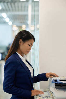 Young business woman printing out important documents