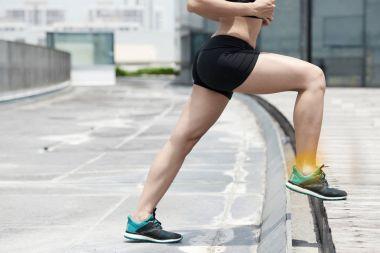 Woman training outdoors, painful leg