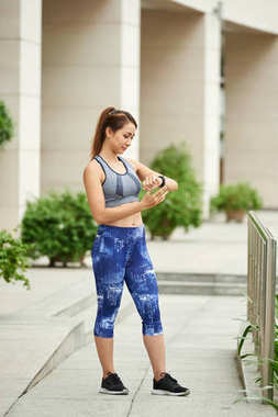 Fit Asian young woman setting her tracker before jogging