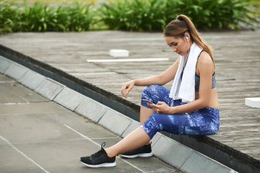 Female jogger checking statistics of training in mobile application