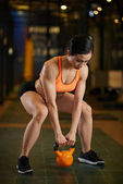 Photo Vietnamese sporty woman doing squats with kettlebell