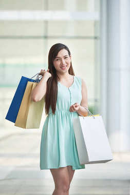 Portrait of lovely pretty Asian woman with shopping bags