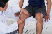 Doktor kontrolu kolenního kloubu z mužské sportovce
