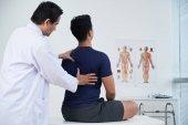 Doktor kontrola hřbetu mladého muže v rámci každoroční lékařské prohlídky
