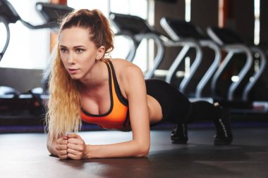 Pretty young woman in plank position in gym
