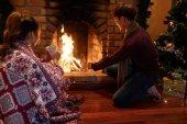 Fotografie Muž přidání dřevo do krbu, aby to pálení na Štědrý večer