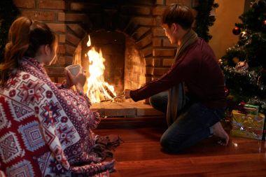 Man adding wood to fireplace to keep it burning on Christmas night