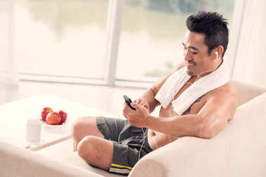 Asian smiling man in headphones sitting on couch and choosing music for sports training