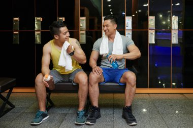 Cheerful friends drinking water and talking in gym locker room after working out