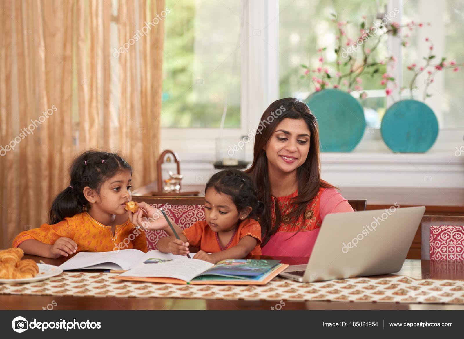 cheerful pretty indian woman working laptop babysitting stock photo