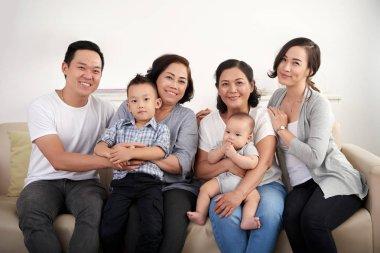 Happy big Vietnamese family sitting on sofa stock vector