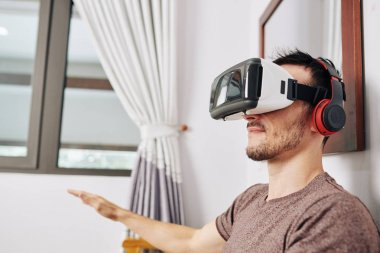 Positive young man wearing VR headset when testing new application he created