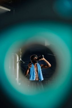 Fit sweaty sportsman drinking fresh water and reading text messages on his smartphone, view through blurred teal circle