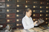 Mature Asian woman counting on abacus when working at counter of traditional Chinese apothecary