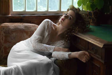 portrait of young woman with curly hair in white dress lying on sofa near window