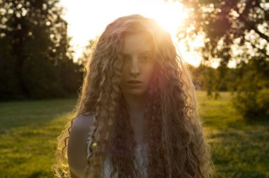 close-up portrait of young sensual woman with curly hair at sunset