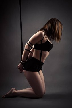 sexy slave woman kneeling with tied hands
