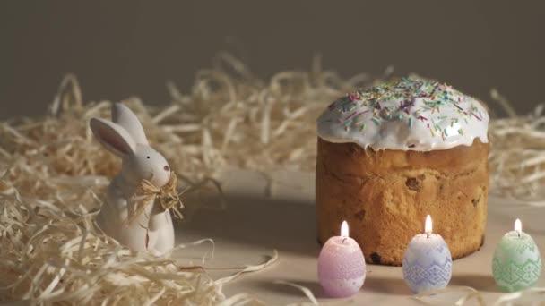 Húsvéti pite gyertyák és a nyúl a fából készült asztal