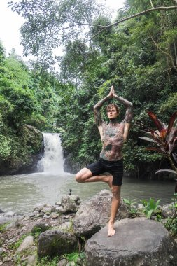 Tattooed man practicing yoga on rock with aling-aling waterfall and green plants on background, Bali, Indonesia stock vector