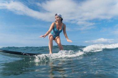 Smiling woman in swimming suit surfing in ocean stock vector